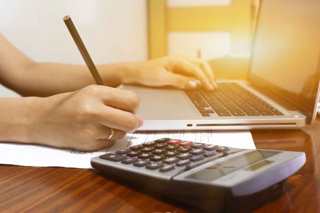 woman working with calculator, business document and laptop computer notebook,business  finance, selective focus